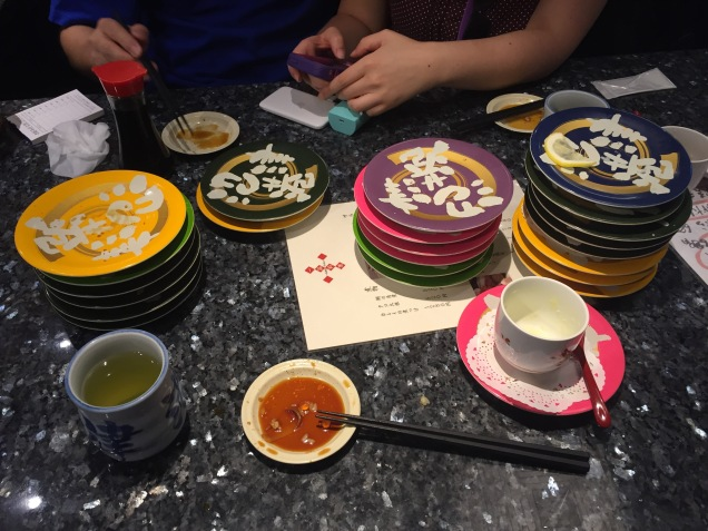 Conveyor belt sushi! Three people go through a lot of plates.